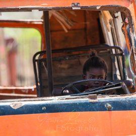 Kleines Mädchen sitz in altem Schrottfahrzeug am Steuer, Madagaskar | Madagascar